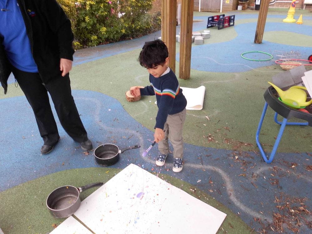 A child splatters paint on to a large piece of paper