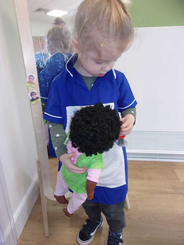 A preschool child dressed up as a nurse cares for a baby doll.