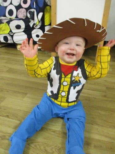 A baby sitting on the floor, dressed up as Woody from Toy Story