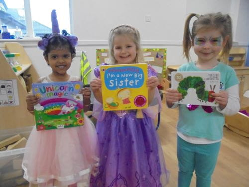 Three young children dressed up as princesses holding up their favourite books for World Book Day