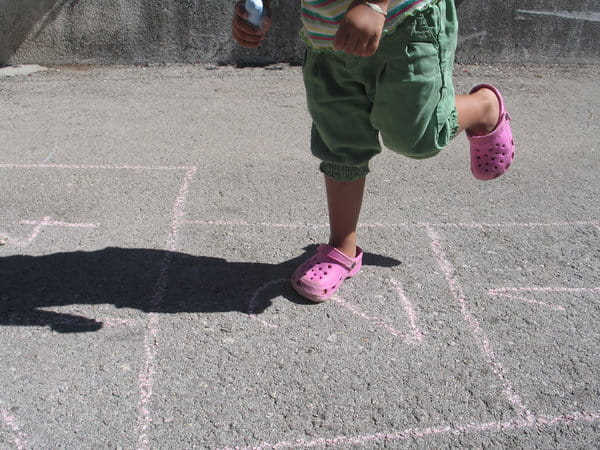 A young child plays hopscotch